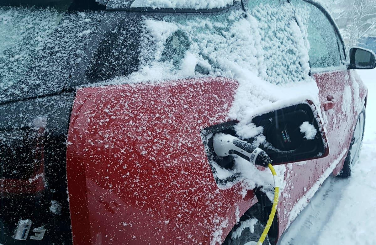 Sähköauton lataus lumisella säällä talvella.