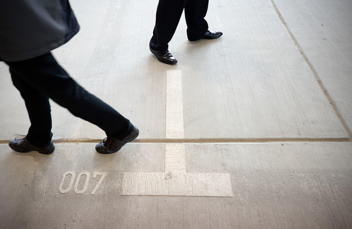 kaksi miestä kävelee parkkipaikalla