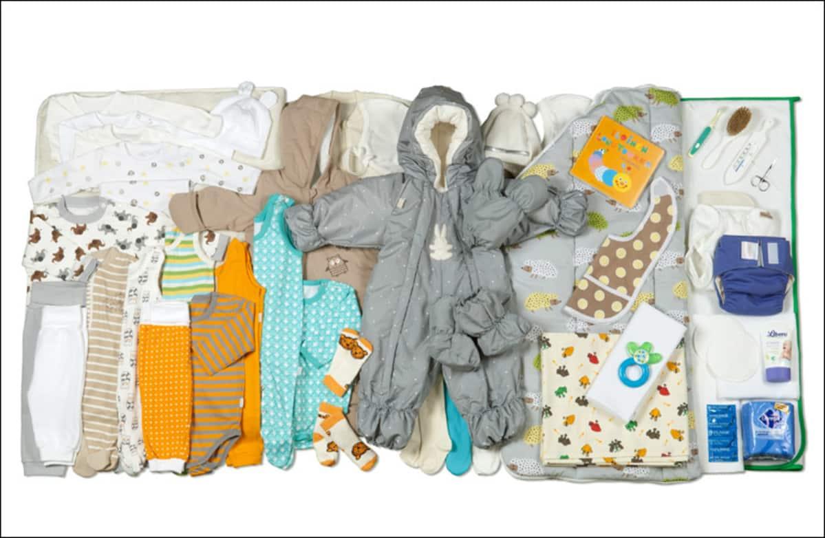 Äitiyspakkaus koko komeudessaan. Mitään punaista uudesta äitiyspakkauksesta ei löydy. Vihreää, oranssia, harmaa, valkoista, sinistä ja ruskeaa väriä vaatteista löytyy.