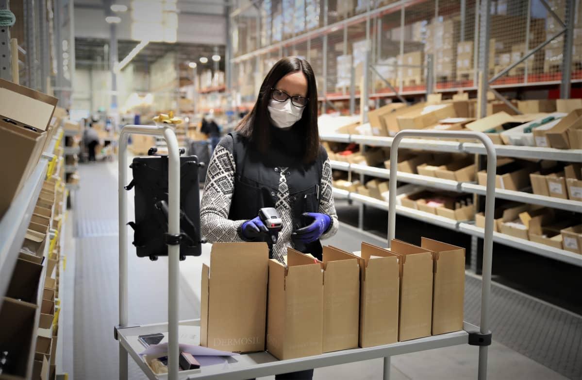 Nainen pakkaa asiakkaan tilaamia tuotteita laatikkoon