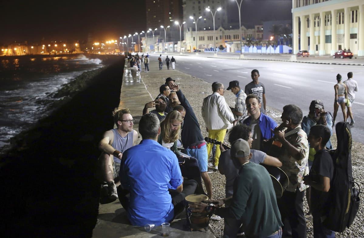 Ihmisiä soittamassa ja laulamassa muutama tunti kuolinuutisen jälkeen Havannassa, Kuubassa 26. marraskuuta.
