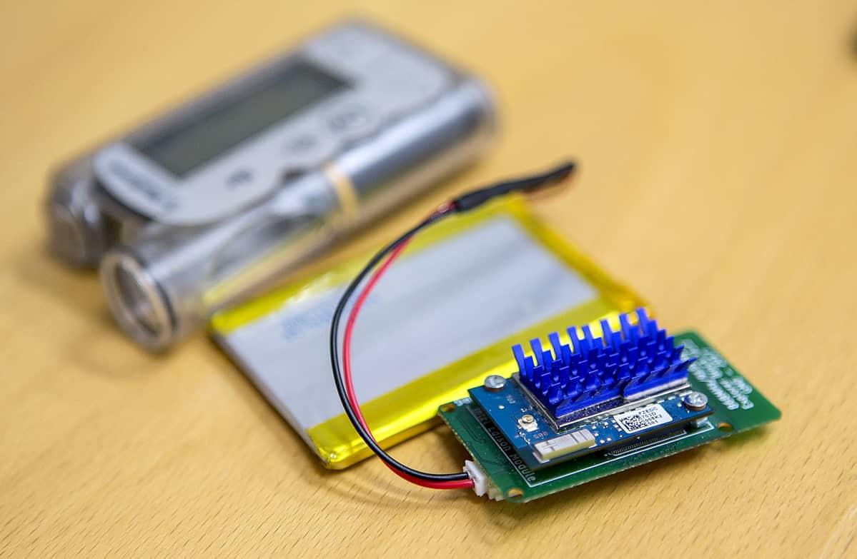 Keinohaimaan kuuluva prosessori, taustalla akku ja insuliinipumppu.