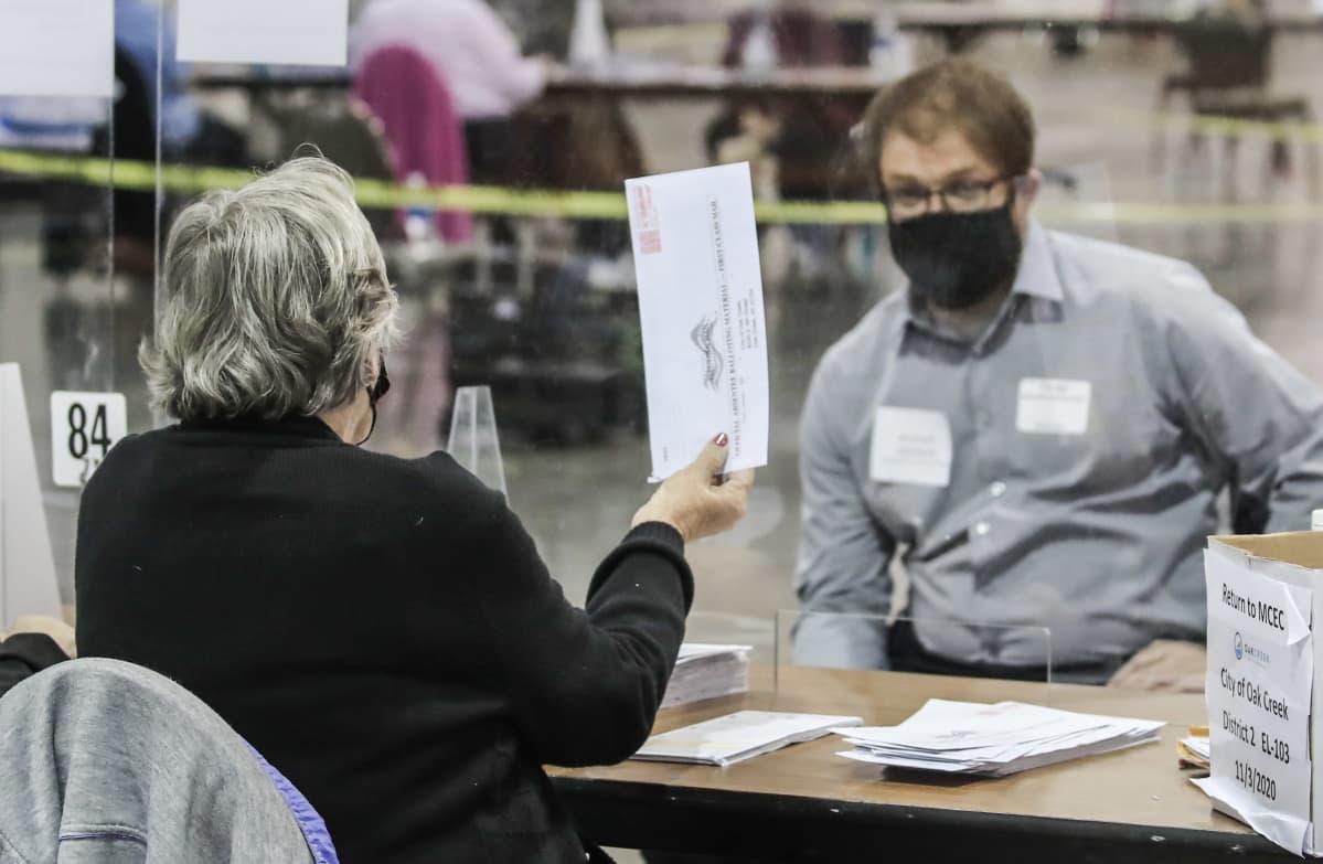 Ääntenlaskija näyttää vaalilippua pleksin läpi vaalitarkkailijalle Wisconsinissa.