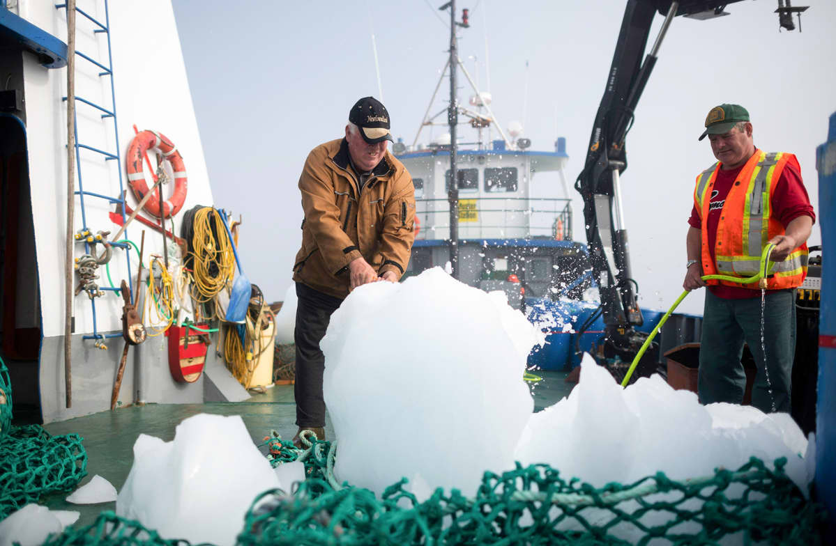 Kaksi miestää pilkkoo veneessä jäävuoresta irronnutta palasta.