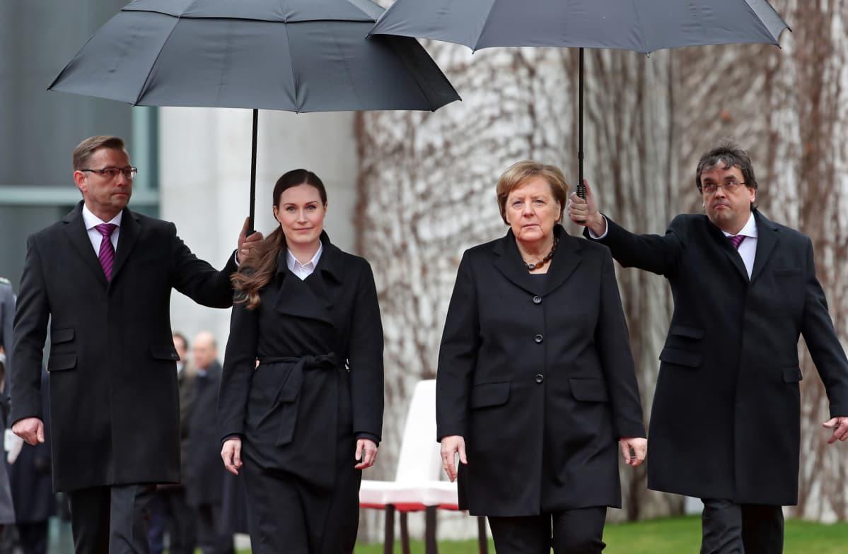 Sanna Marin ja Angela Merkel miesten pitelemien sateenvarjojen alla.