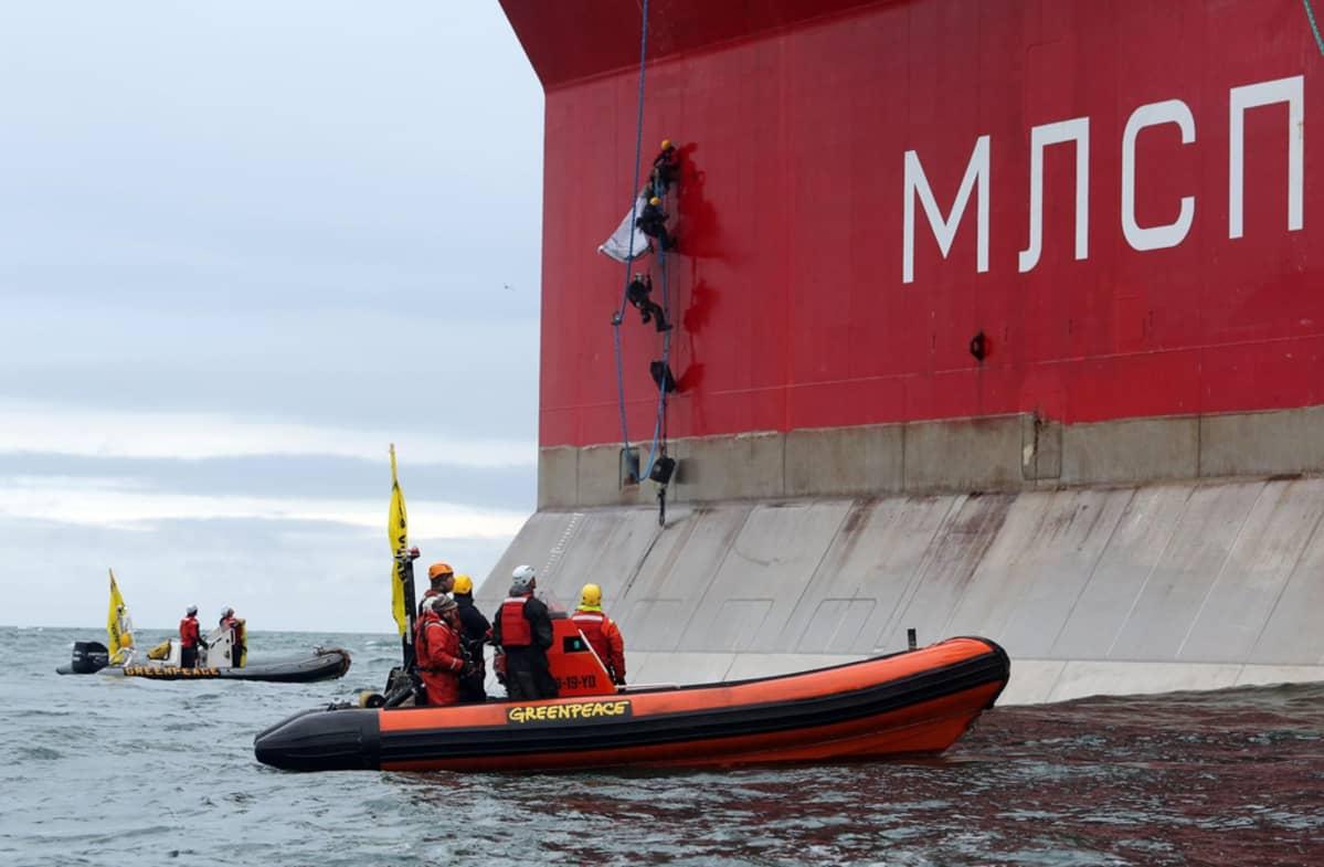 Greenpeacen aktivistit, joiden joukossa suomalaisaktivisti Sini Saarela ja Greenpeacen pääsihteeri Kumi Naidoo, nousemassa öljynporauslautta Prirazlomnajalle Petsoranmerellä.
