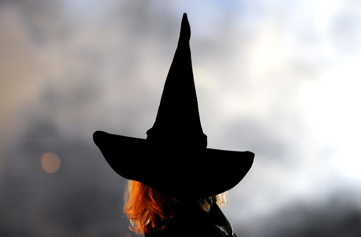 Musta, korkea, noitamainen hattu kuvattuna vaaleaa taustaa vasten.