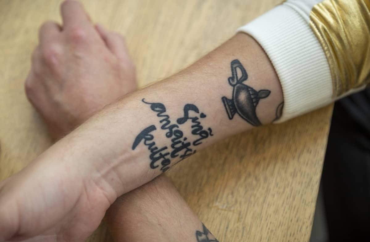 """Homopojan oppaan kirjoittajan Eino Nurmiston kädet, joissa tatuointi, jossa lukee """"Sinä ansaitset kultaa""""."""