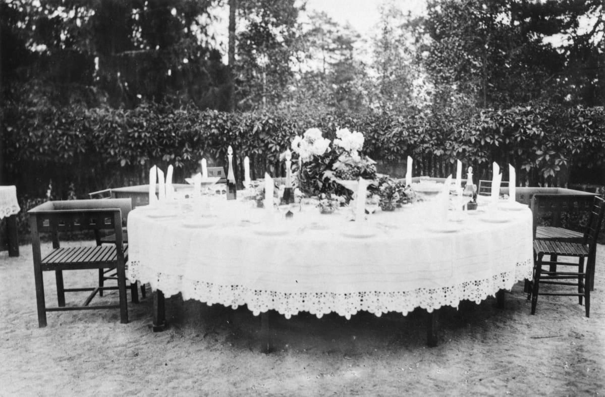 Kauniisti katettu ruokapöytä Hvitträskin terassilla.