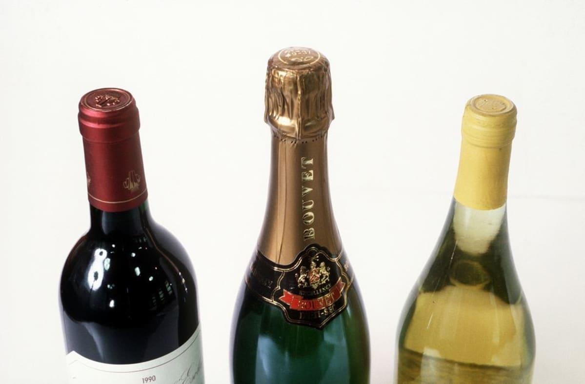 Kolme pulloa, joissa on puna- ja valkoviiniä sekä samppanjapullo.