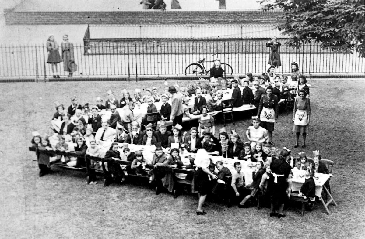 Ihmisiä istumassa kahdessa pitkässä juhlapöydässä, jotka on aseteltu V:n muotoon.