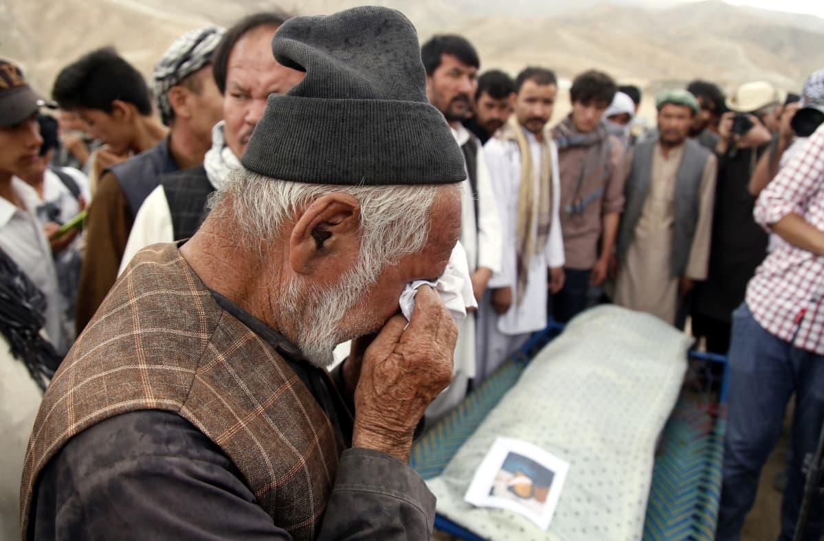 Kuvassa hazaramies itkee hautajaisissa. Taustalla muita miehiä.