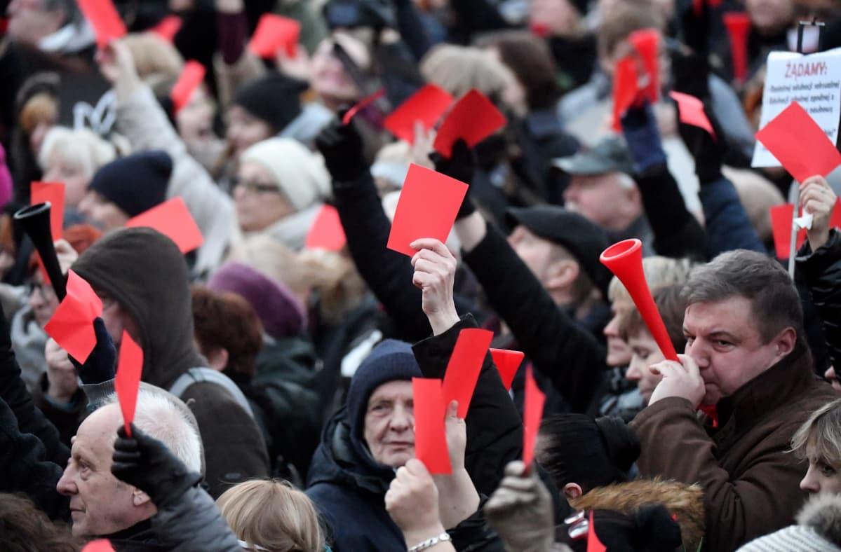 Miehet ja naiset näyttävät punaista korttia.