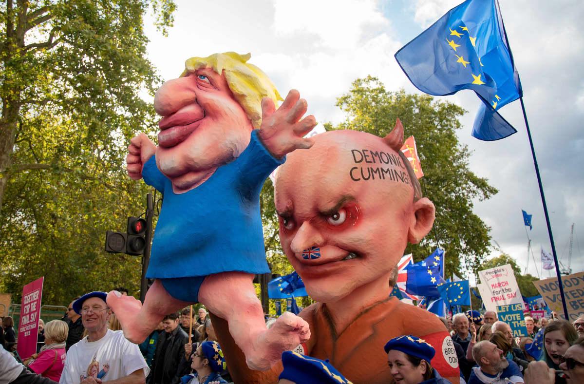 Mielenosoitukset kuljettavat kahta suurta hahmoa, jotka esittävät Britannian pääministeriä ja tämän neuvonantajaa. Cummings on esitetty natsimaisena hahmona, joka ohjailee Boris Johnsonia kuin nukkea.