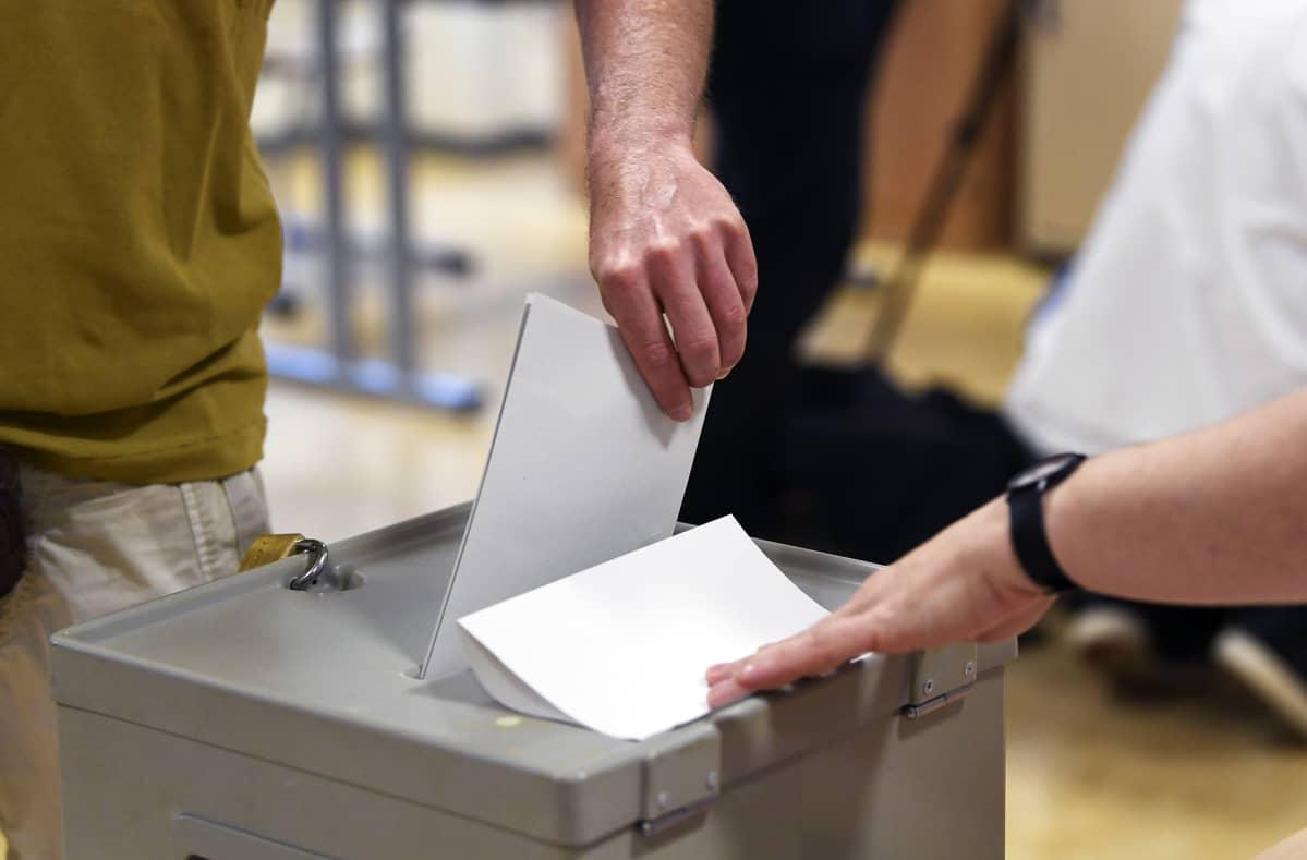 ÄÄnestäjä pudottaa lipukkeen vaaliuurnaan.