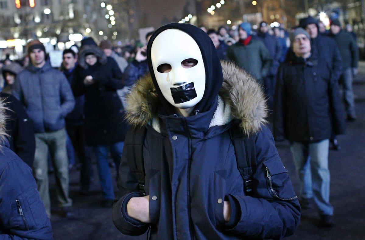 Naamioitunut nuori mies osallistui mielenosoitukseen Romanian pääkaupungissa Bukarestissa sunnuntaina 29.1.2017.