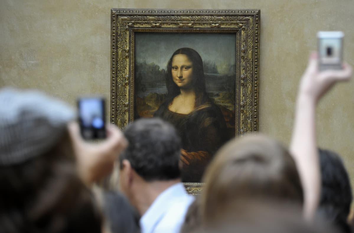 Ihmiset parveilevat Mona Lisan edessä. Osa kuvaa kännykällä.