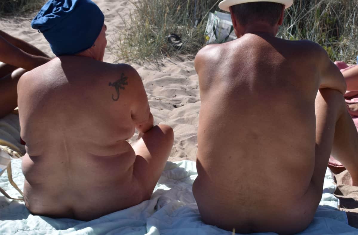 mies ja nainen istuvat alastomina rannalla