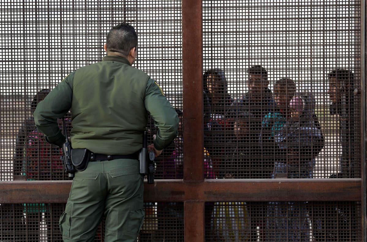 Rajavartija keskustelee Yhdysvaltoihin pyrkivien maahanmuuttajien kanssa Teksasin El Pasossa.