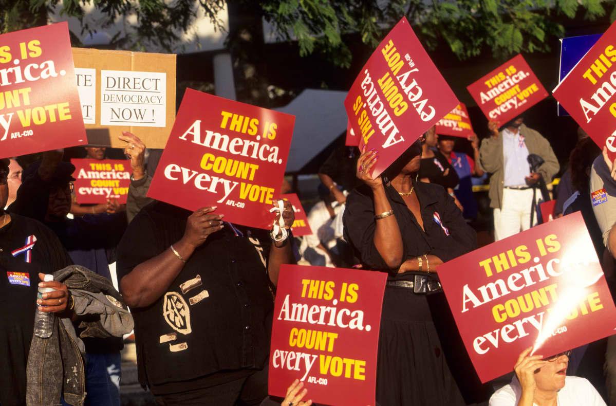 Mielenosoittajat punaisten kylttien kanssa vaativat, että kaikki äänet on laskettava.
