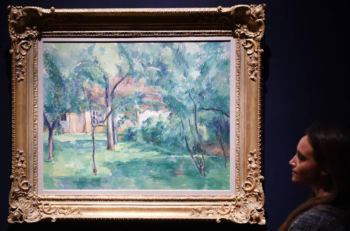 Nainen katselee koristeellisesti kehystettyä öljymaalausta, joka esittää taloa puiden takana.