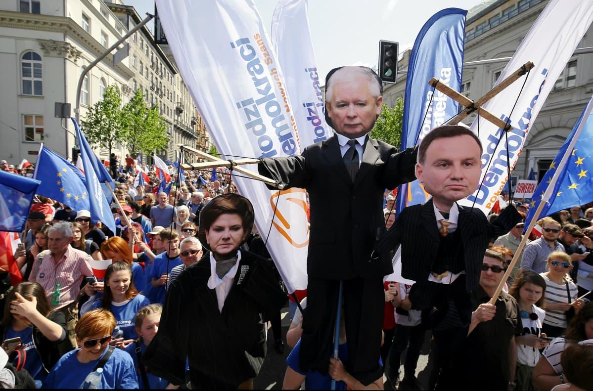 Suuri joukko ihmisiä kulkee katua pitkin. Ihmisillä on käsissään muun muassa EU-lippuja. Etualalla kannetaan isoja nukkehahmoja. Jarosław Kaczyńskia esittävä nukke riiputtaa pääministeriä ja presidenttiä esittäviä nukkeja naruista.