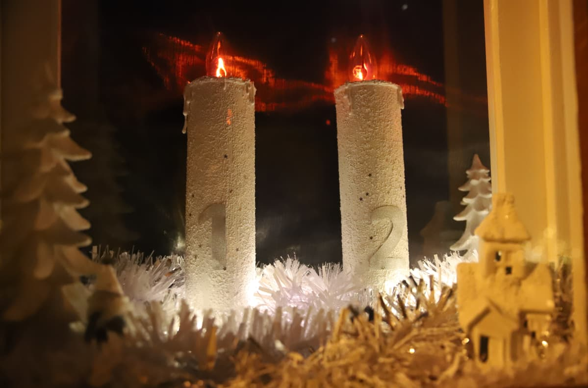 jouluikkunassa kaksi kynttilää