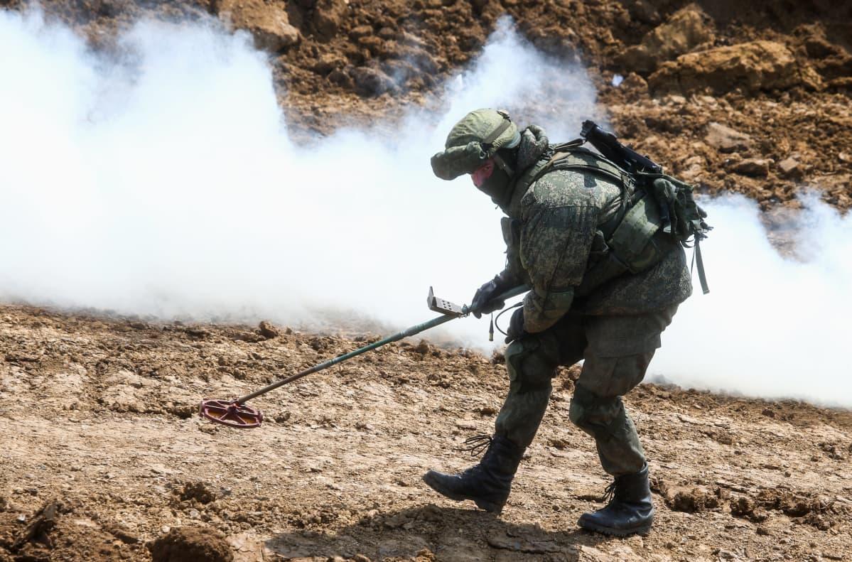 Sotilas kulkee tutkien maastoa metallinpaljastimen kanssa. Hänen taustallaan näkyy savua.