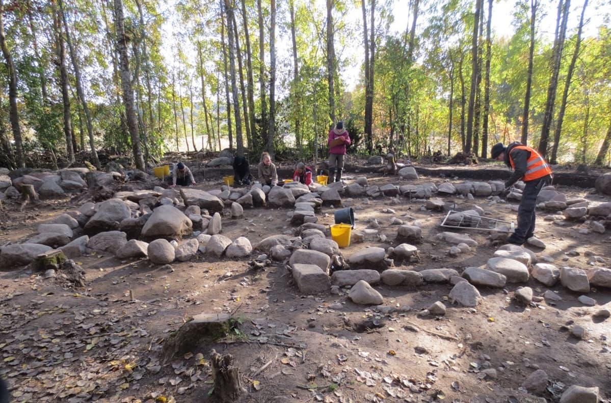 Arkeologeja kaivamassa koivmetsään raivattua aluetta, jossa on suuria kivenmurikoita,  muinaisen kirkon kivijalkaa.