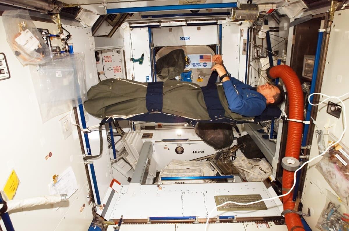 Mies makuulla avaruusaseman rakenteisiin vöillä kiinnitetyssä makuupussissa. Hänen kätensä leijuvat ilmassa.