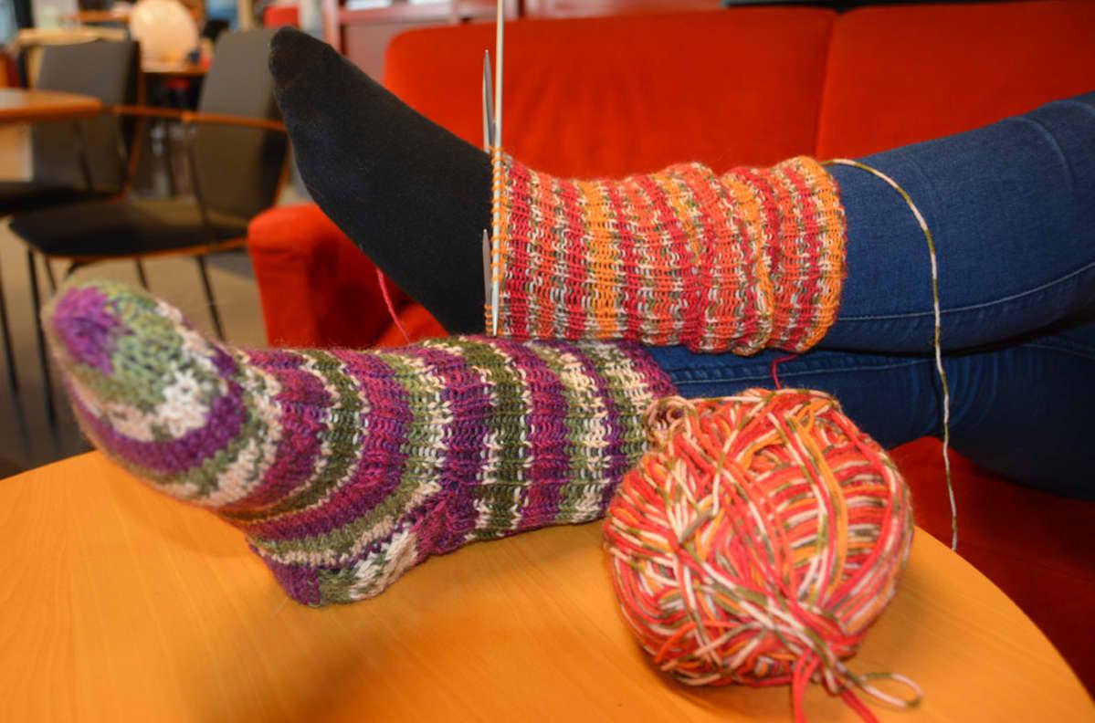 Kuvassa jalat, joista toisessa valmis villasukka ja toisessa puolivalmis sukka.