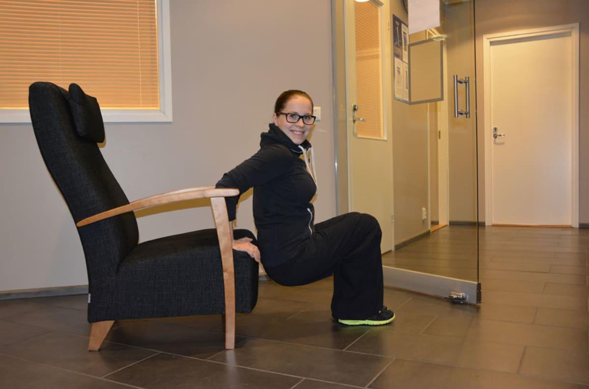 Annukka Harinen tekee dippiliikettä tuolin reunalla.