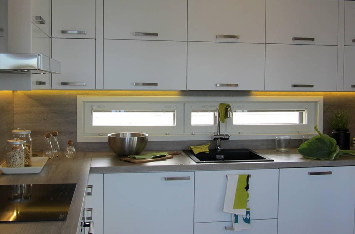 Kuvassa valko-keltainen keittiö