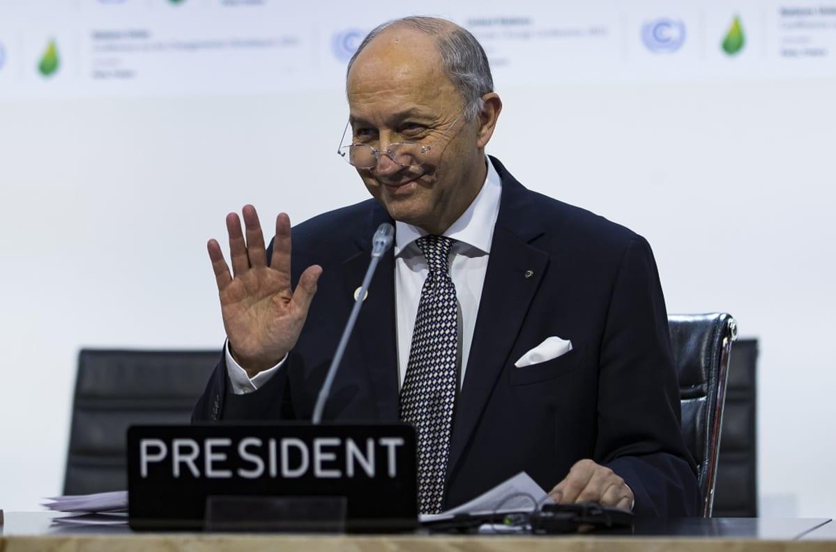 Ranskan ulkoministeri Laurent Fabius Pariisin ilmastokokouksessa. Tummaan pukuun ja pilkulliseen kravattiin pukeutunut Fabius hymyilee. Hänen silmälasinsa ovat matalalla nenän päällä ja hän pitää oikeaa kättään hieman ylhäällä olkapään tasolla, kämmen kameraan päin. Ulkoministerin edessä pöydällä on mikrofoni. Tausta on valkoinen, siinä näkyy ilmastokokouksen vihreitä logoja.
