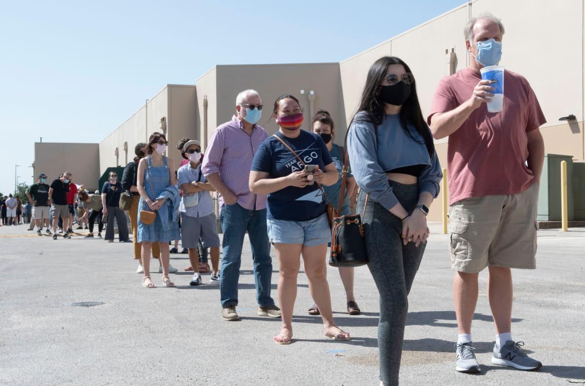 Teksasilaisia jonottaa pitkässä jonossa ennakkoäänestämään. Ihmiset pitävät turvaetäisyyksiä ja kaikilla on kasvomaskit.