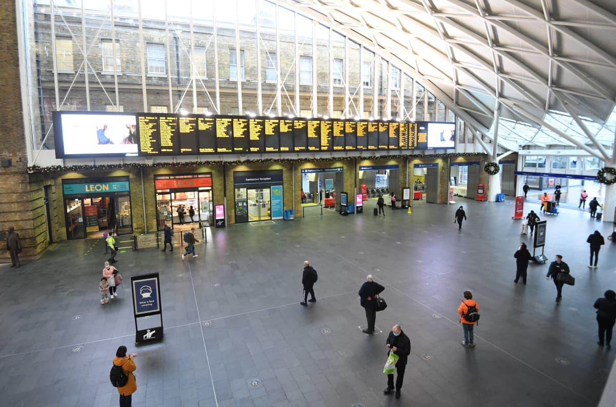 King's Crossin rautatieasemalla Lontoossa oli hiljaista 21. joulukuuta 2020. Muutama ihminen odotti jonossa pääsyä pohjoiseen kulkeviin juniin.