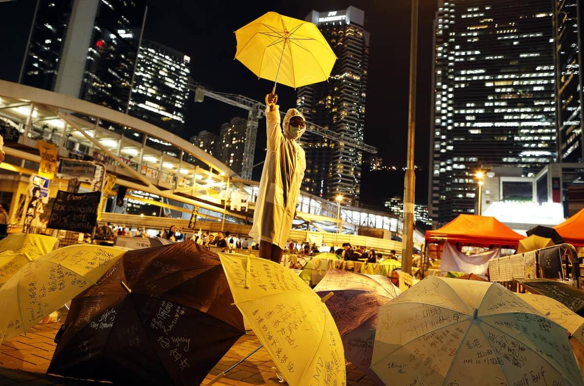 Mielenosoittaja pitelee keltaista sateenvarjoa.