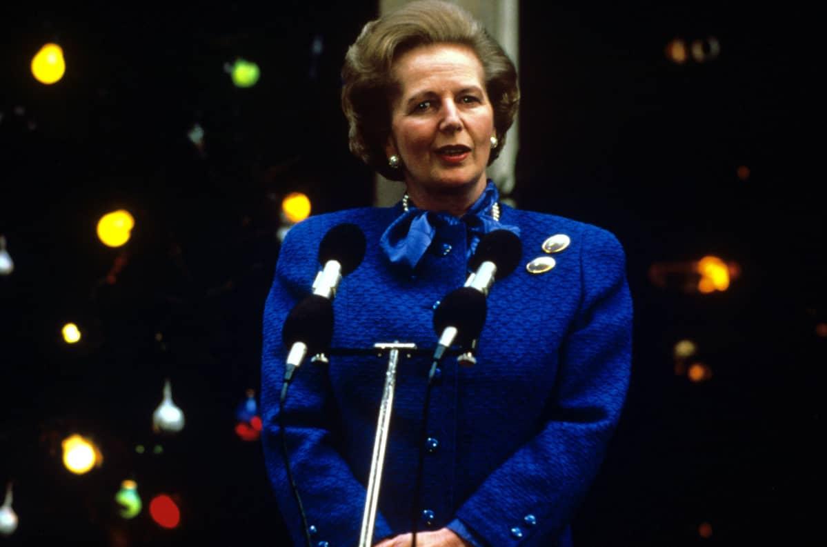 Siniseen asuun pukeutunut Thatcher puhumassa.