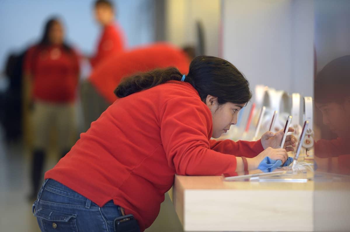 Myyjä puhdistaa älypuhelimia Applen myymälässä..