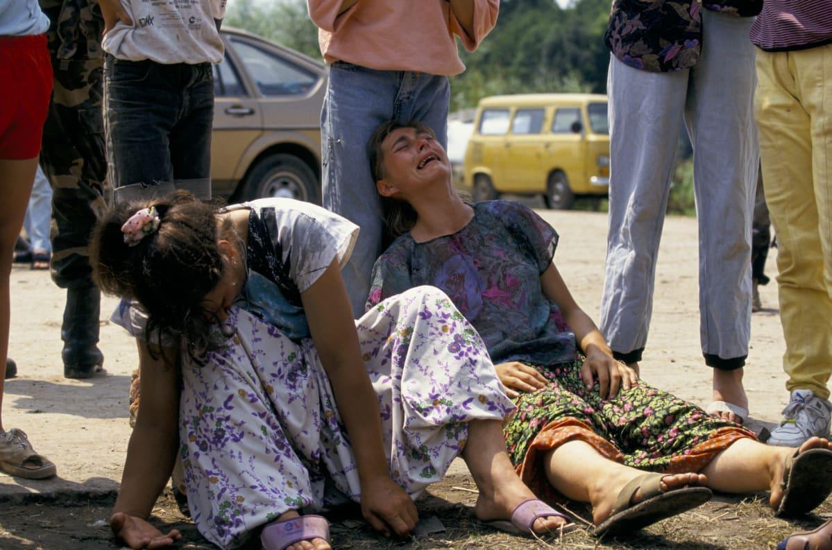 Bosnialaisnaiset itkevät kuultuaan läheistensä kuolleen Srebrenican joukkomurhassa heinäkuussa 1995. Naiset istuvat kuvan etualalla maassa, heidän takanaan on seisovia ihmisiä.