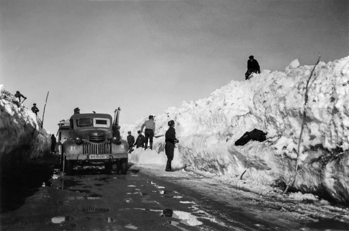 Miehiä lapioimassa lunta Jäämerentieltä. Tiellä on kuorma-auto. Petsamo 1942 tai aikaisemmin.