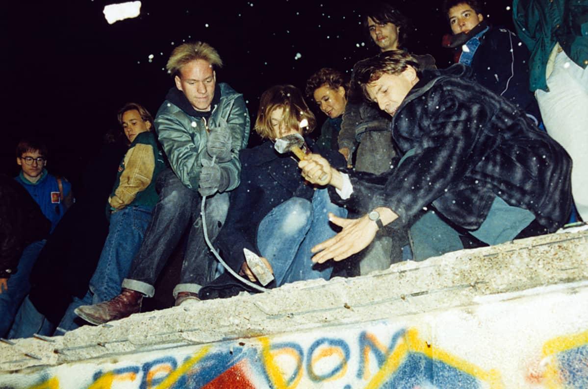 Länsiberliiniläisiä Berliinin muurin päällä.