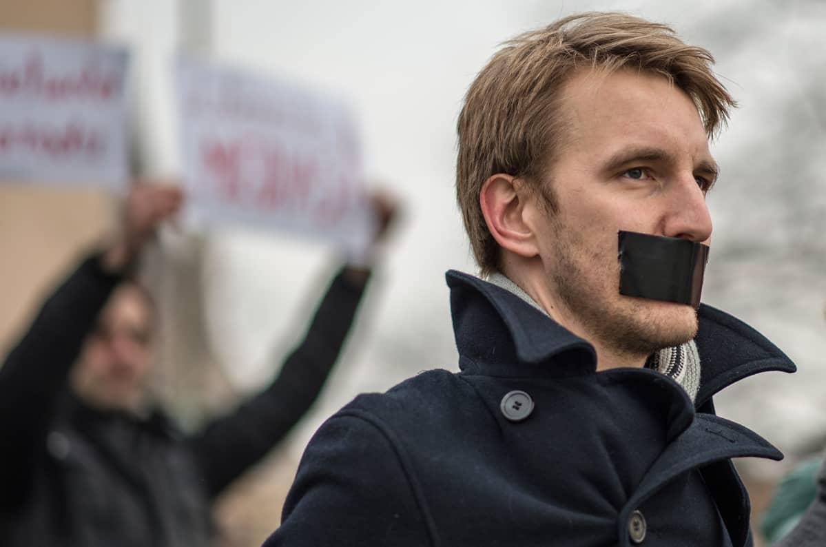 Mies on teipannut suunsa mustalla teipillä.