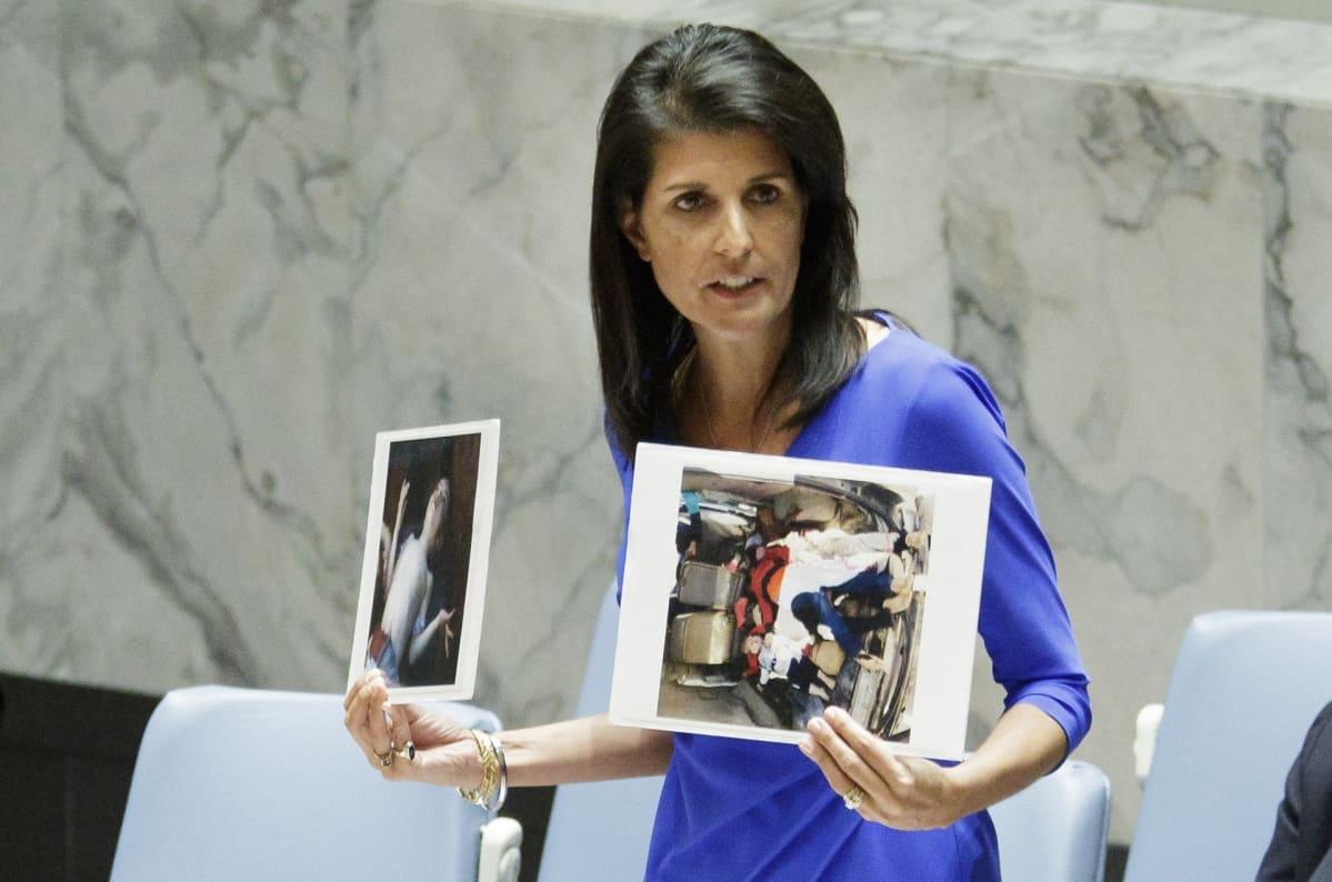 Nikki Haley seisoo kokouspöydän takana ja pitää käsissään kahta valokuvaa.