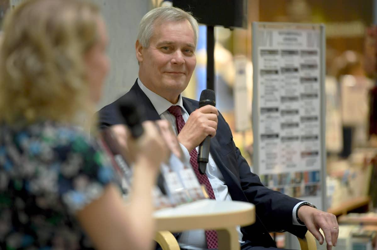 Antti Rinne sitter på en scen och håller i en mikrofon.
