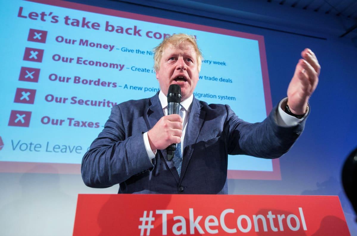 """Boris Johnson puhuu Vote Leave -kampanjan tilaisuudessa, Puhujankorokkeessa on teksti """"Take control"""" eli """"Ota kontrolli""""."""