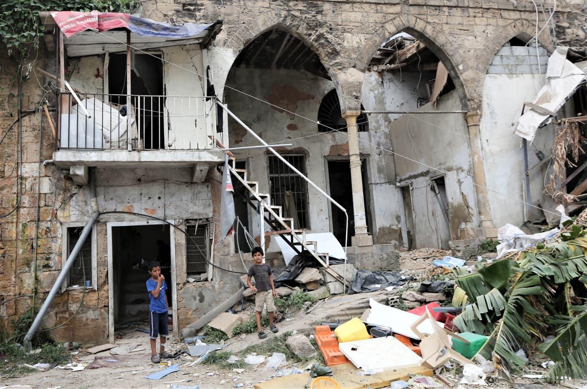 Syyrialaisia lapsia seisoo vahingoittuneen talon luona Karantina alueella, lähellä räjähdyspaikkaa 9. elokuuta.