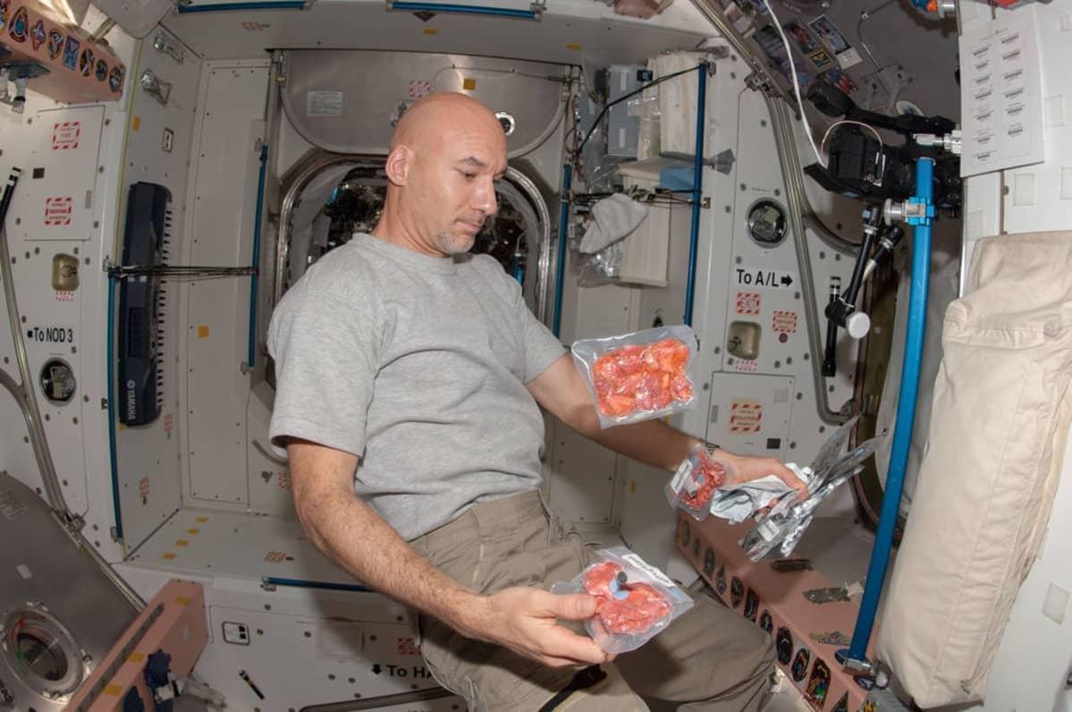 Astronautti leijailee istuma-asennossa avaruusaseman sisällä. Hänellä on käsissään useita pakkauksia pakastekuivattua ruokaa, ja kaksi pakkausta leijailee ilmassa.