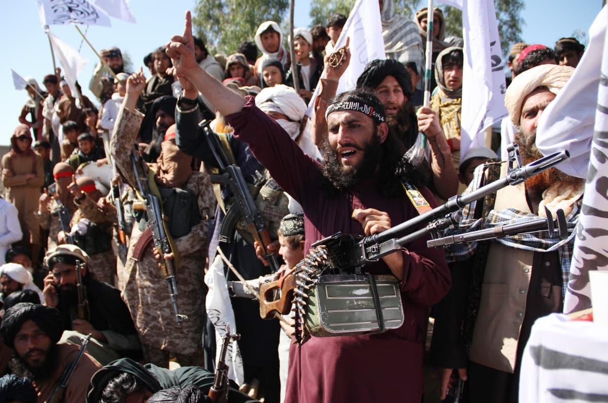 Afghanistanilaiset Taliban-sotilaat ja kyläläiset juhlivat Yhdysvaltain ja Talibanin välistä rauhansopimusta.