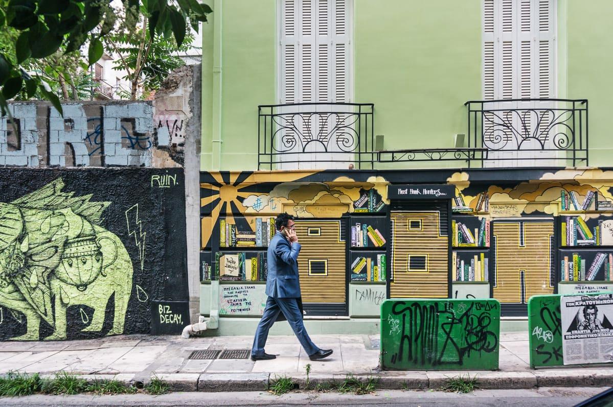 Mies kävelee graffitiseinän edessä.